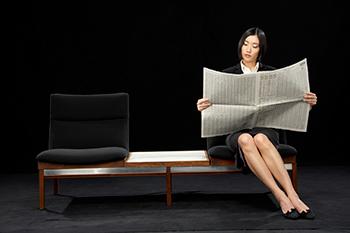 Businesswoman sitting on bench reading newspaper, News
